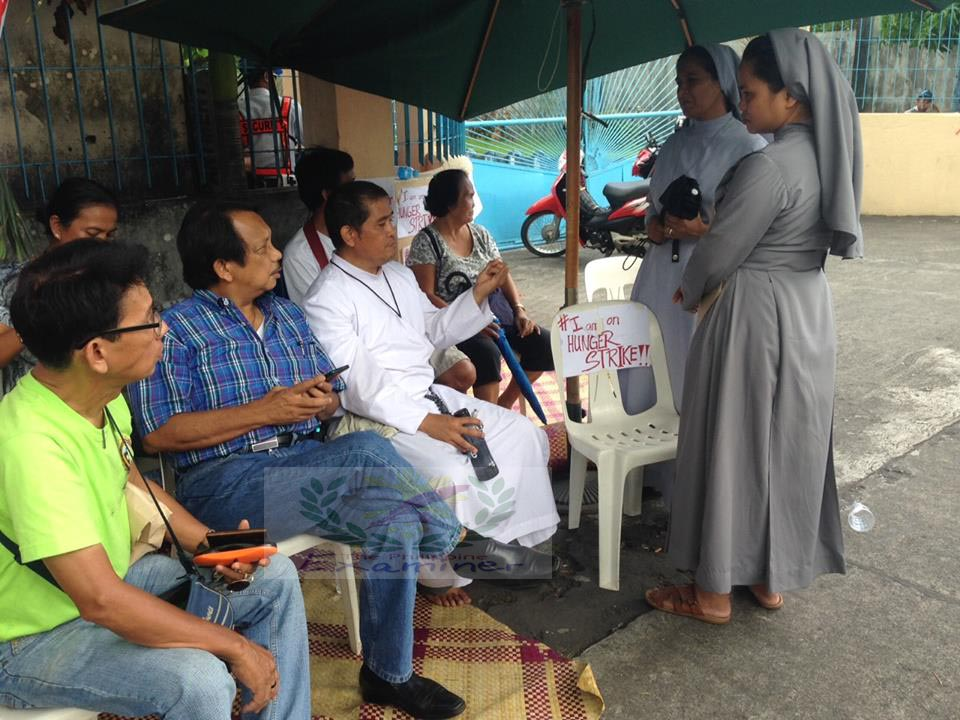 Hunger Strike on the Picketline: Reverend Father Oliver Castor, [C.Ss.R], [center] VACC Chair, Dante Jimenez and Demetrio C. Reynoso of CroW talks with nuns in the picketline.