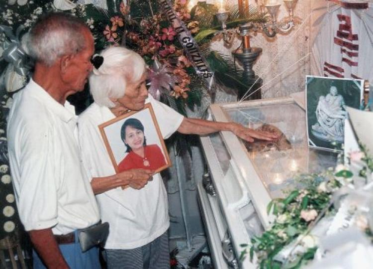Pacencia Garcia holds a photograph of her slain daughter, Marlene Esperat, as she and her husband attends the ral wake after she was killed in a brutal execution-style killing in the Philippines in 2005. (Mark Navales/AFP/Getty Images)